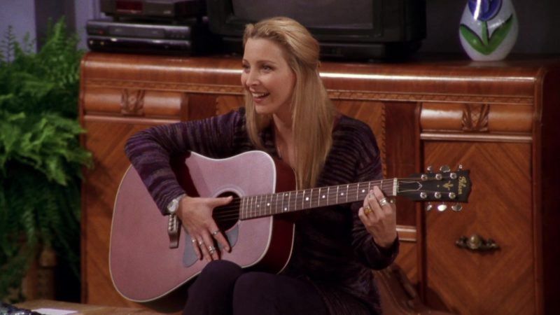 """Gibson Acoustic Guitar Held by Lisa Kudrow (Phoebe Buffay) in Friends Season 4 Episode 7 """"The One Where Chandler Crosses the Line"""" (1997) - TV Show Product Placement"""