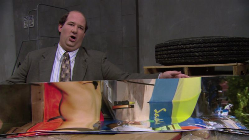 """Sandals Resorts International Poster Held by Brian Baumgartner (Kevin Malone) in The Office – Season 3, Episode 12, """"Back from Vacation"""" (2007) TV Show Product Placement"""