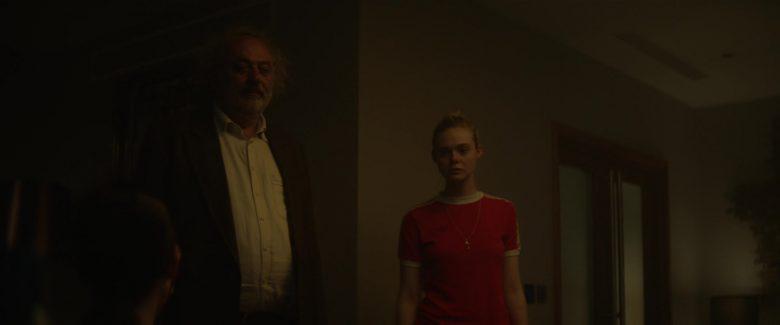 Elle Fanning standing in a dark room
