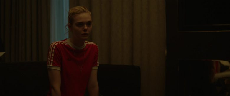 Elle Fanning standing in front of a curtain