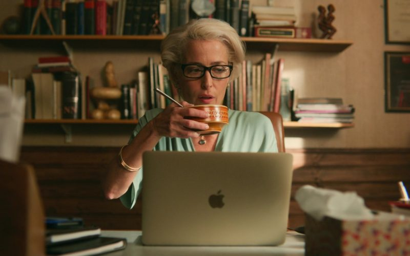 Gillian Anderson sitting at a table using a laptop