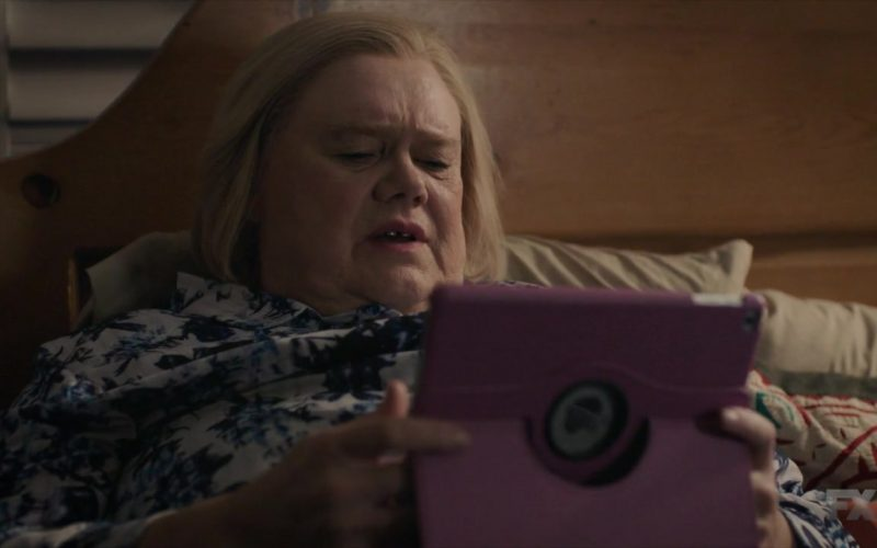 Louie Anderson sitting on a bed