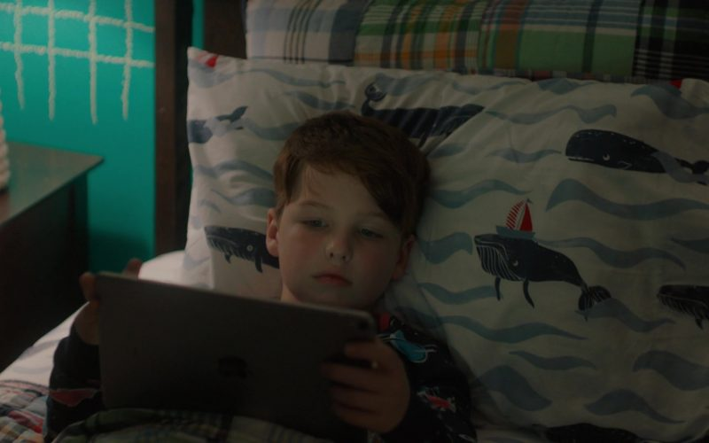 A boy lying on a bed using a laptop