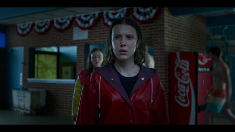 Millie Bobby Brown in a red rain coat