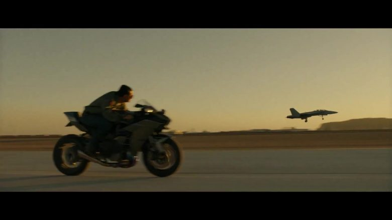 A fighter jet flies through the air while riding a motorcycle