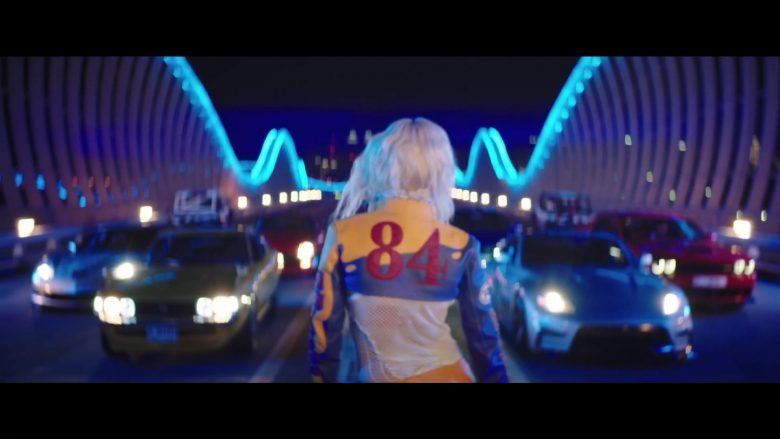 Moschino Cropped Racing Leather Jacket and Blue Moto Leggings Worn by Rita Ora in New Look (2019) - Official Music Video Product Placement