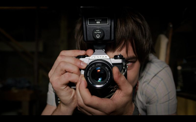 A man holding a camera in front of a mirror posing for the camera