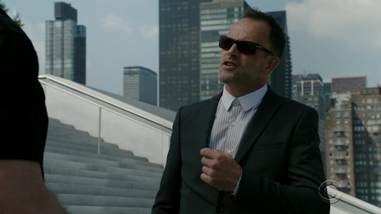A man wearing a suit and sunglasses standing outside of a building