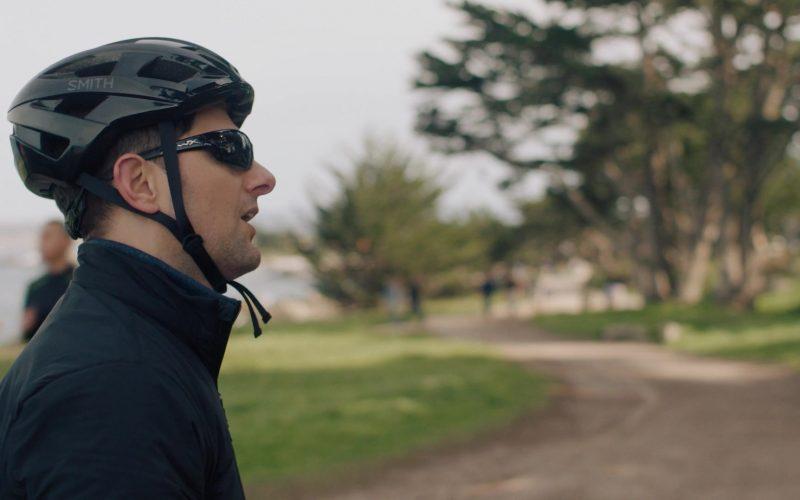 A man wearing a bike helmet and sunglasses