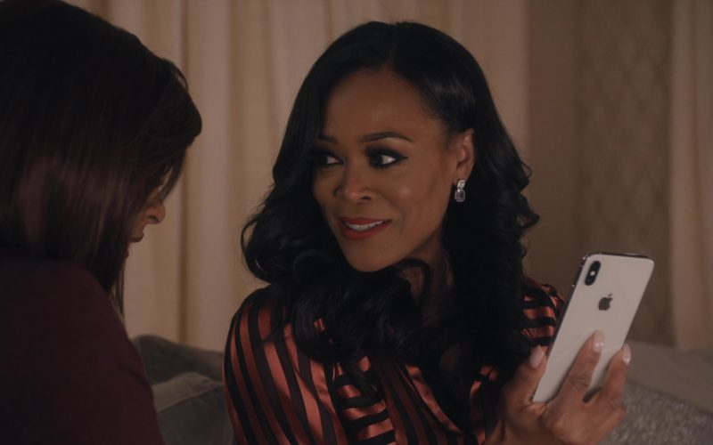 Robin Givens holding a iphone