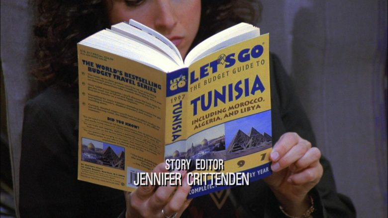 Let's Go The Budget Travel Guide To Tunisia Held by Julia Louis-Dreyfus as Elaine Benes in Seinfeld Season 8 Episode 17
