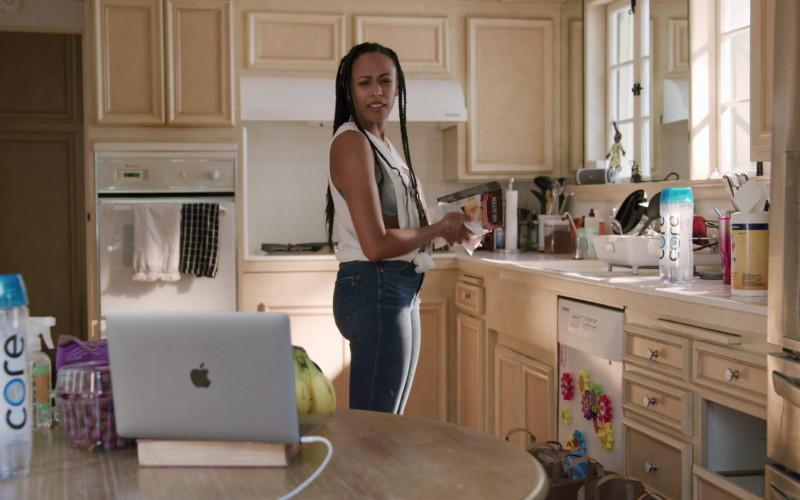 Core Water and Apple MacBook Laptop of Nicolette Robinson as Sade in Love in the Time of Corona S01E01
